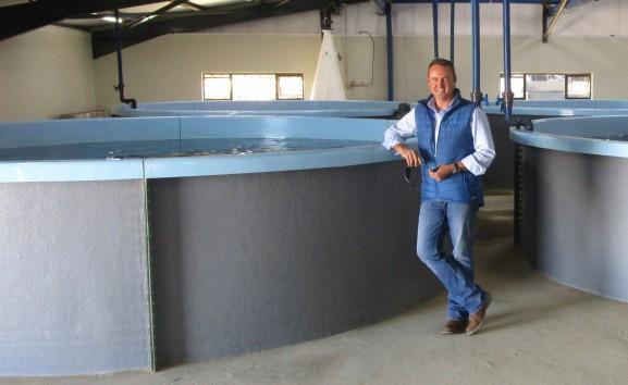 Бодрый и позитивный дядька стоит возле бассейнов с рыбой радуясь новому генератору кислорода и жизни в целом